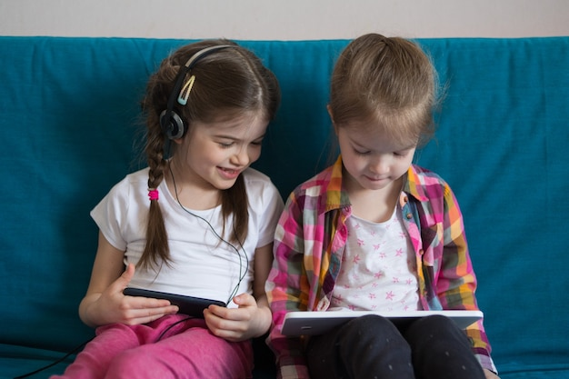 Little girl watching cartoons on a tablet and playing games