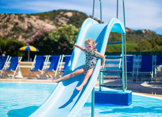 Little girl on water slide at aquapark on summer holiday