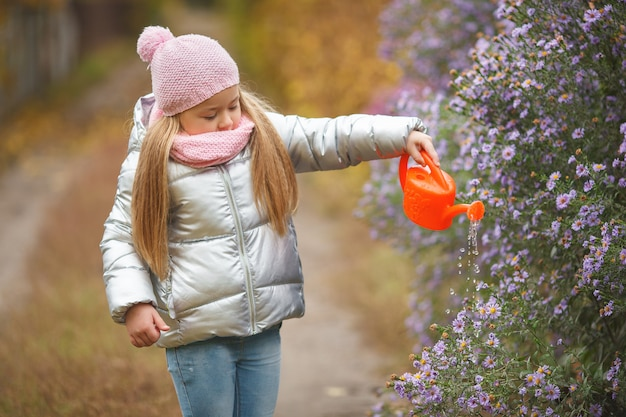 Little girl watering the flowers in the garden in the autumn