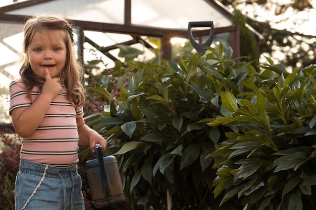 여름에 그녀의 장난감 물을 깡통에서 정원에서 꽃을 급수 하는 어린 소녀