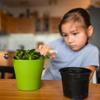 냄비에 식물을 급수하는 어린 소녀