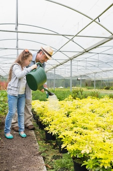 祖父と植物に水をあてる少女