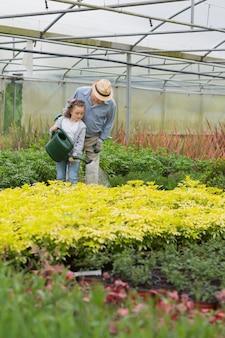 祖父と温室で植物を育てる少女