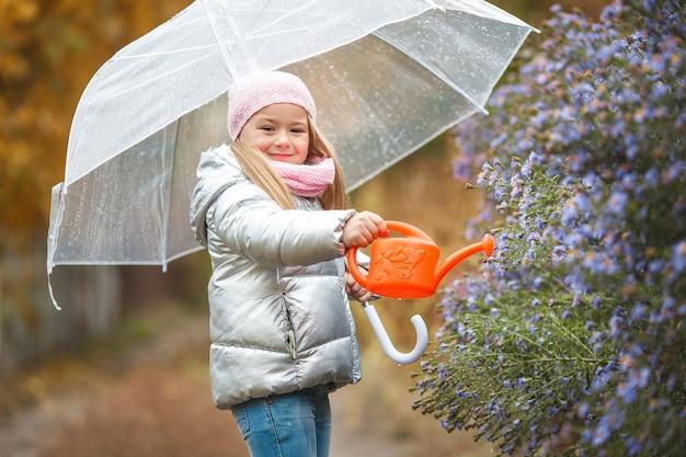 秋の庭の花に水をまく少女