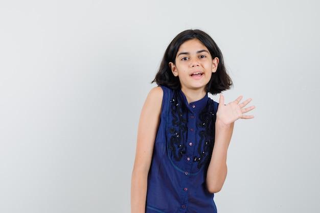 Маленькая девочка машет рукой для приветствия в синей блузке и радуется.