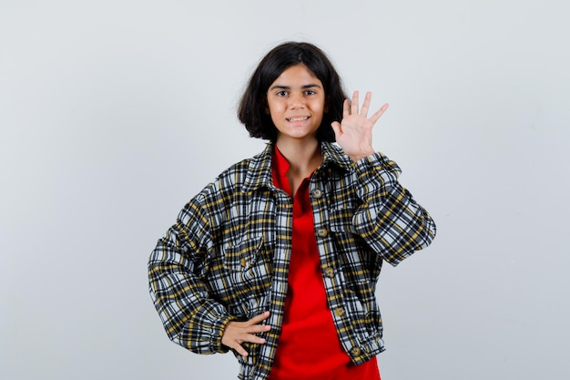 シャツ、ジャケットの正面図で挨拶のために手を振る少女。