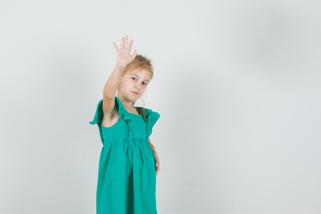 Little girl waving hand to say goodbye in green dress