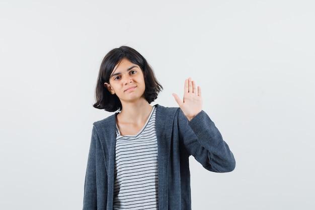 Bambina agitando la mano per dire addio in t-shirt, giacca e guardando fiducioso