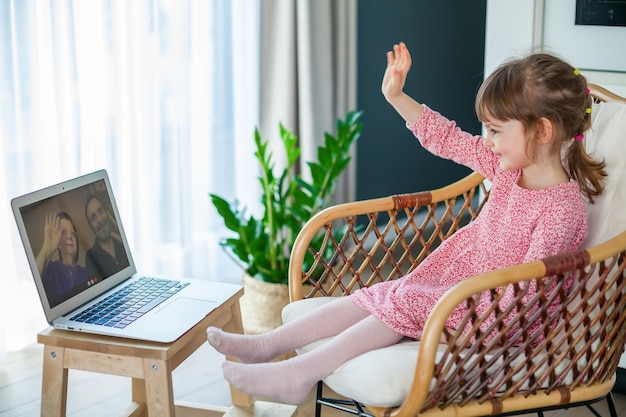 Little girl waving to her grandparents while video-chatting with them using laptop
