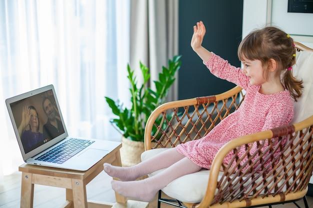 Маленькая девочка машет бабушке и дедушке во время видеочата с ними на ноутбуке