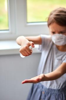 少女は衛生的なマスクを着用し、アルコールスプレーを押して保護し、消毒します。