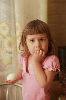 겁 먹은 표정으로 분홍색 티셔츠를 입은 어린 소녀가 부엌에 서 있다