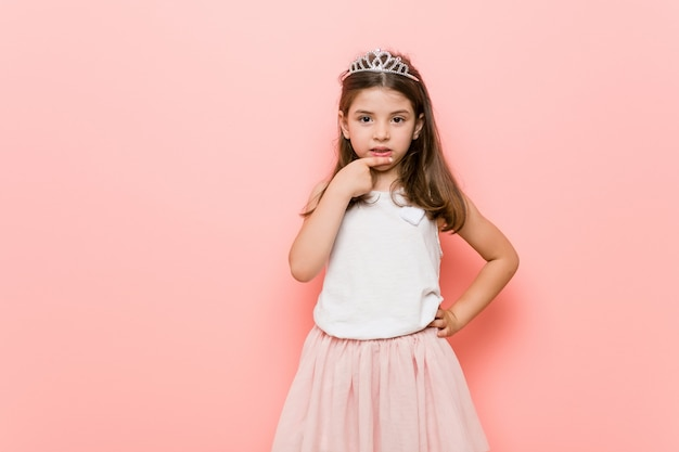 Маленькая девочка, одетая в принцессу, грызет ногти, нервничает и очень беспокоится