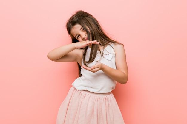 製品のプレゼンテーション、両手で何かを保持しているプリンセスルックを着ている少女。
