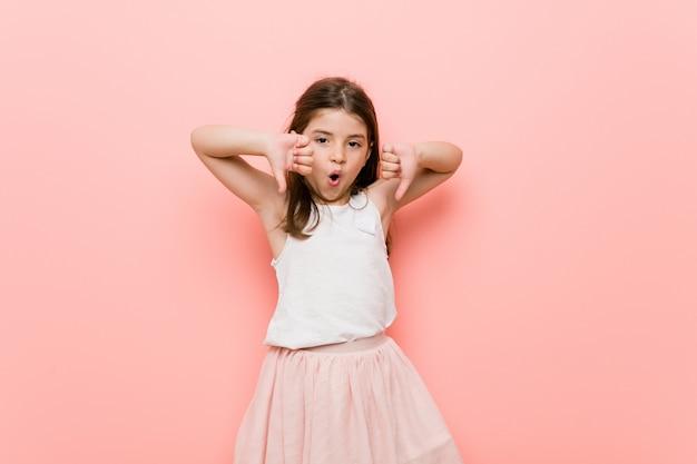 Маленькая девочка носить взгляд принцессы, показывая большой палец вниз и выражая неприязнь.