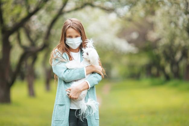 코로나 바이러스 전염병으로 인해 보호 마스크를 착용 한 어린 소녀가 야외에서 개와 함께 혼자 걷고 있습니다.