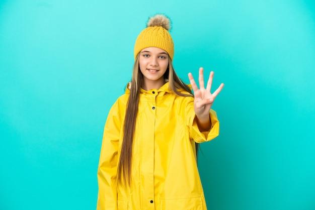 幸せな孤立した青い背景の上に防雨コートを着て、指で4を数える少女