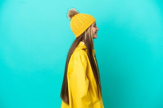 외진 파란색 배경 위에 방수 코트를 입은 어린 소녀가 옆에서 웃고 있다