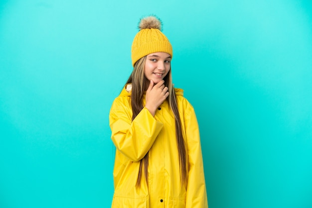 横を見て笑っている孤立した青い背景の上に防雨コートを着ている少女
