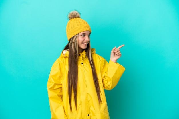 孤立した青い背景の上に防雨コートを着て、指を横に向けて製品を提示する少女