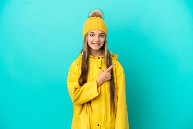 제품을 제시하기 위해 측면을 가리키는 외진 파란색 배경 위에 방수 코트를 입은 어린 소녀