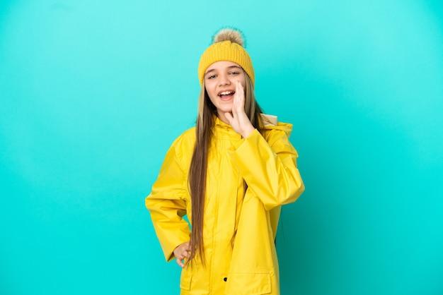 口を大きく開いて叫んで孤立した青い背景の上に防雨コートを着ている少女