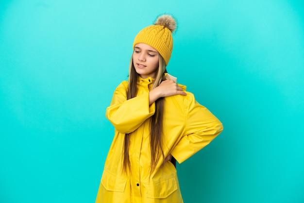 努力したために肩の痛みに苦しんでいる孤立した青い背景の上に防雨コートを着ている少女