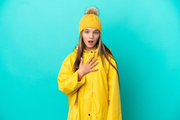 격리된 파란색 배경 위에 방수 코트를 입은 어린 소녀가 오른쪽을 바라보는 동안 놀라고 충격을 받았습니다