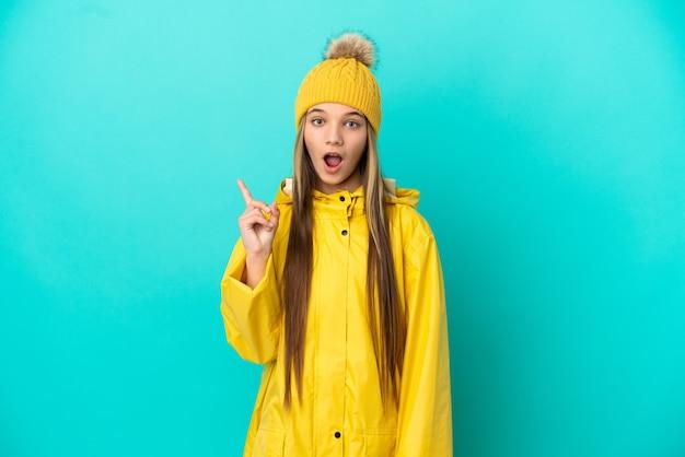 指を上に向けるアイデアを考えて孤立した青い背景の上に防雨コートを着ている少女