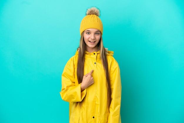 驚きの表情で孤立した青い背景の上に防雨コートを着ている少女