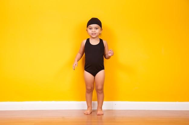 黄色の壁にビーチの衣装を着ている少女