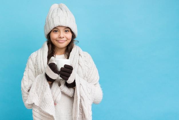 毛布を着て、お茶とカップを保持している少女
