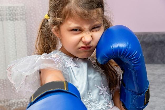 파란색 권투 장갑을 끼고 별이 있는 홀리데이 드레스를 입은 어린 소녀