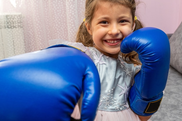 Little girl wearing blue boxing gloves and a holiday dress with stars