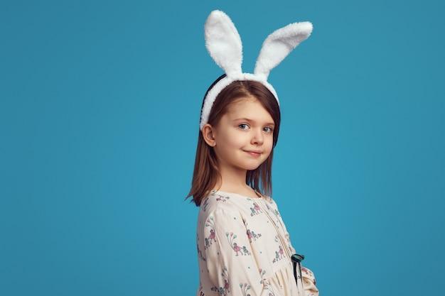 Маленькая девочка с кроличьими ушками и позирует на синей стене