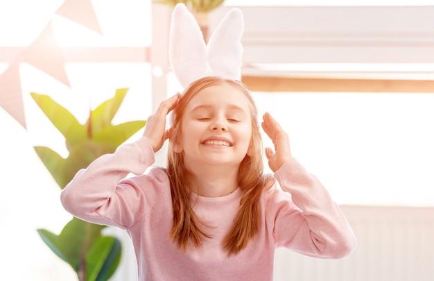 부활절 날에 햇볕이 잘 드는 방에서 웃고있는 토끼 귀를 입고 어린 소녀