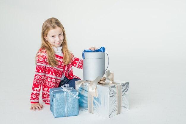 Маленькая девочка в рождественском свитере сидит изолированно на белой поверхности