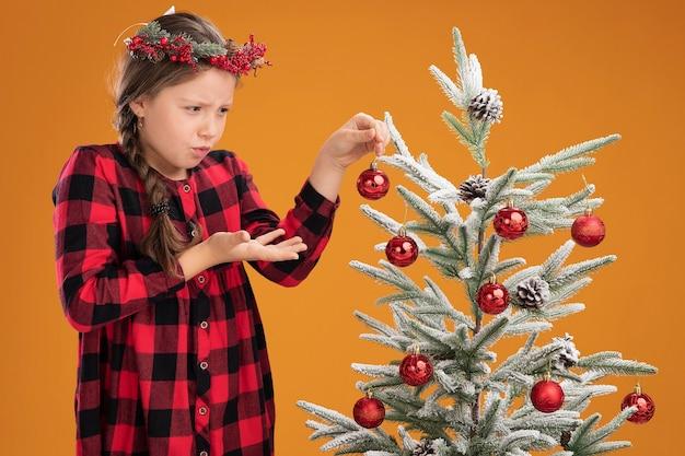 Bambina indossa la corona di natale in abito controllato che decora l'albero di natale cercando confuso e molto ansioso in piedi su sfondo arancione