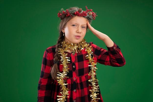 首に見掛け倒しのチェックドレスでクリスマスリースを着ている少女は、間違いのために彼女の頭の上の手と混同