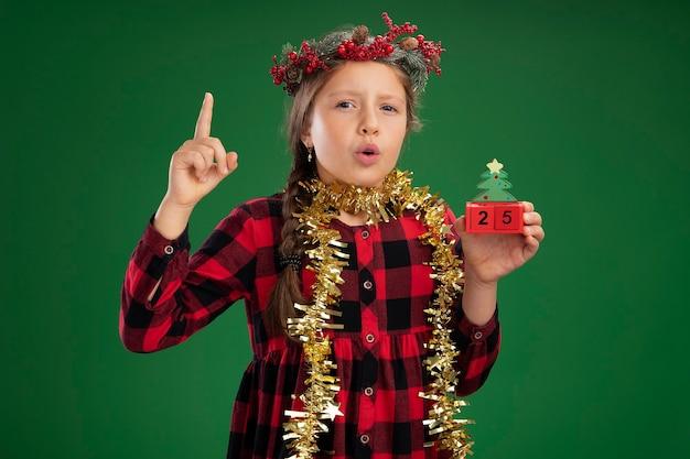 Маленькая девочка в рождественском венке в клетчатом платье с мишурой на шее держит игрушечные кубики с удивленным свиданием, показывая указательный палец