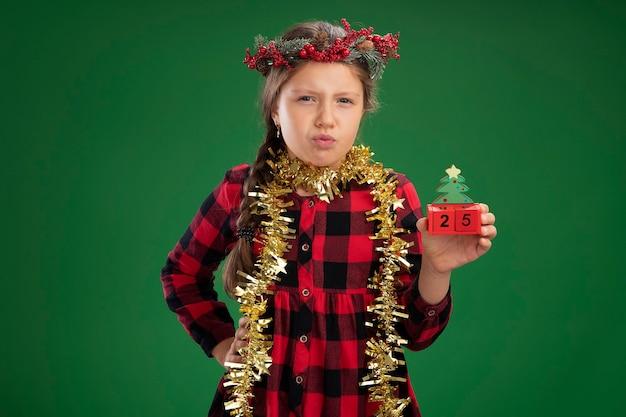 Маленькая девочка в рождественском венке в клетчатом платье с мишурой на шее держит игрушечные кубики с рождественским свиданием с серьезным выражением лица