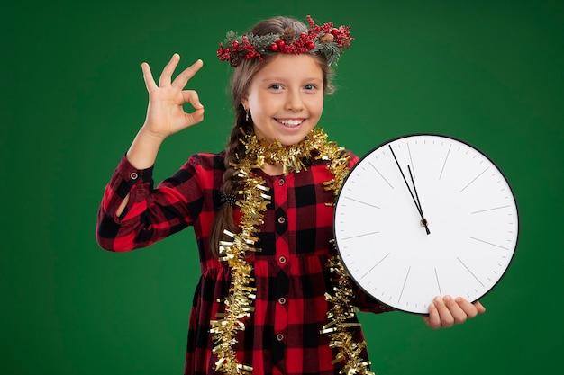 Маленькая девочка в рождественском венке в клетчатом платье с мишурой на шее держит настенные часы, глядя в камеру с улыбкой на лице, показывая знак ок, стоящий на зеленом фоне