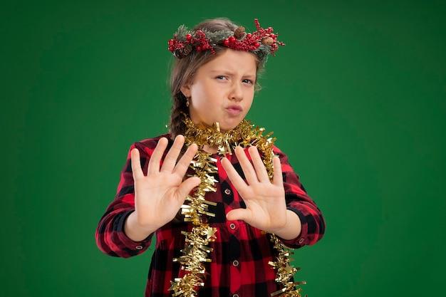 Маленькая девочка в рождественском венке в клетчатом платье с мишурой на шее, глядя в камеру, обеспокоена, делая защитный жест руками, стоящими на зеленом фоне