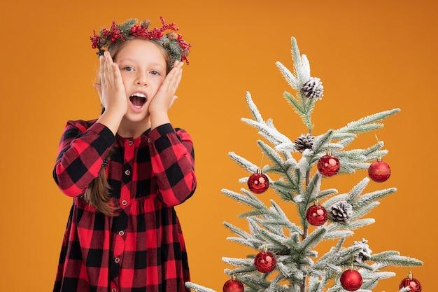 Маленькая девочка в рождественском венке в клетчатой рубашке изумленно стоит рядом с елкой над оранжевой стеной