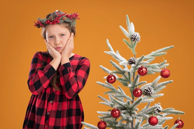 Маленькая девочка в рождественском венке в клетчатой рубашке счастлива и позитивно стоит рядом с елкой над оранжевой стеной
