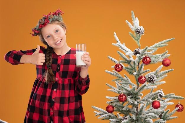 오렌지 벽 위에 크리스마스 트리 옆에 서있는 엄지 손가락을 유쾌하게 보여주는 우유 한 잔을 들고 체크 셔츠에 크리스마스 화환을 입은 어린 소녀