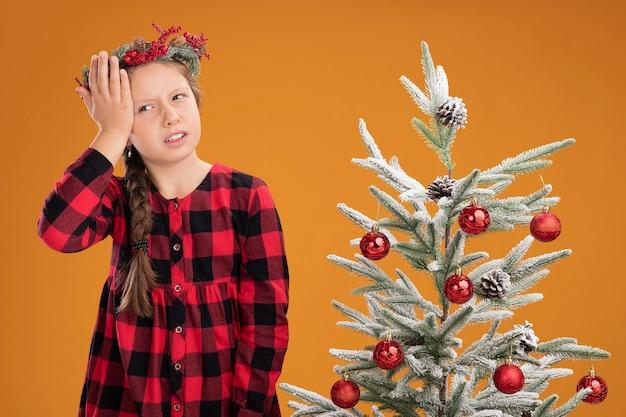 Маленькая девочка в рождественском венке в клетчатой рубашке выглядит смущенной, положив руку на голову, стоя рядом с елкой над оранжевой стеной