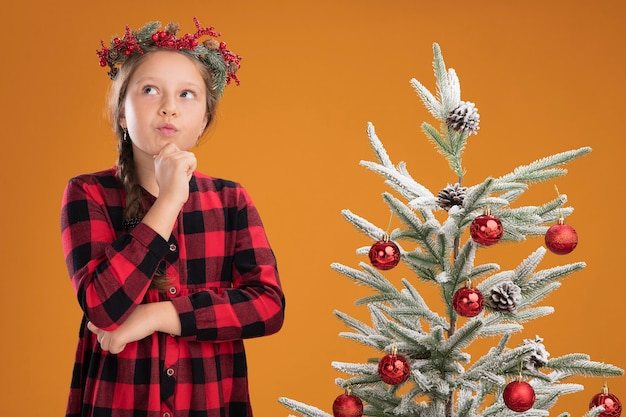 オレンジ色の壁の上のクリスマスツリーの横に立って困惑して見上げるチェックシャツにクリスマスリースを着ている少女