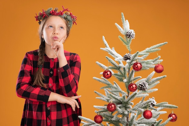 Маленькая девочка в рождественском венке в клетчатой рубашке смотрит озадаченно, стоя рядом с елкой над оранжевой стеной