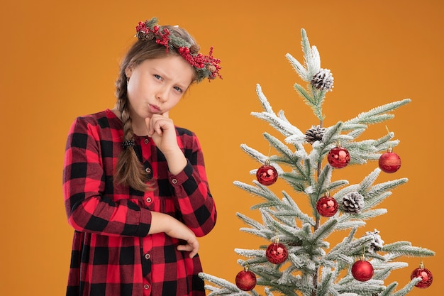 오렌지 벽 위에 크리스마스 트리 옆에 서 심각한 얼굴로 턱 생각에 손으로 체크 셔츠에 크리스마스 화 환을 착용하는 어린 소녀